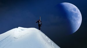 Person climbs snowy mountain towards the summit