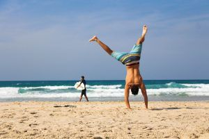 Young man does cartwheel at the beach