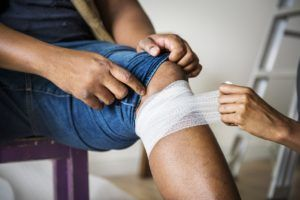student wrapping injured leg