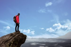 student standing on the peak of a cliff