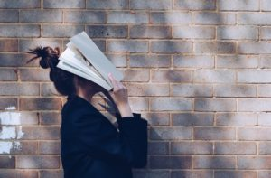 student holding book to her face