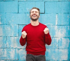 man in red sweater smiling against blue wall