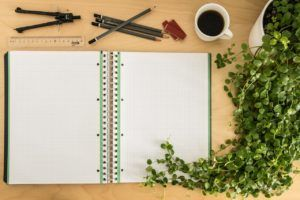 graph pad and writing utensils on desk