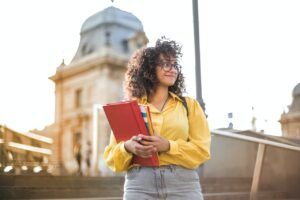 student in yellow holding book