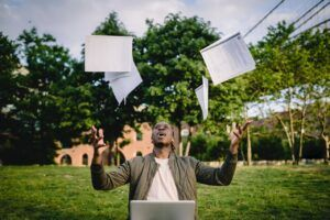student throwing papers in the air while working on computer